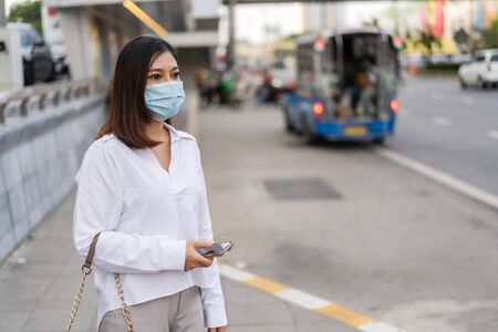 young asian woman holding smartphone and waiting for bus at bus stop in city street and wearing face mask protective for spreading of coronavirus(covid-19) pandemic, new normal concept
