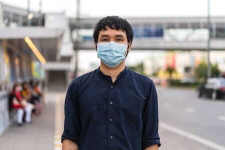 young asian man wearing medical mask for prevention from coronavirus (Covid-19) pandemic on street in the city. new normal concepts