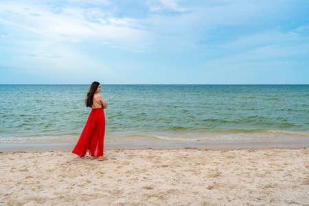 happy woman in red dress standing with arms crossed on the sea beach