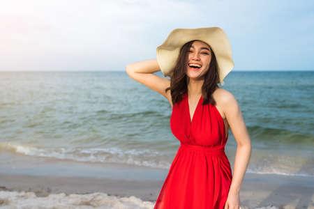 cheerful woman in red dress enjoying on the sea beach