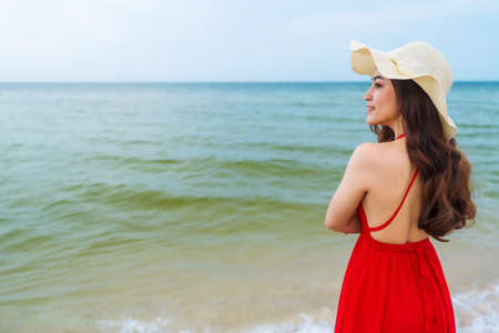 happy woman in red dress standing with arms crossed on the sea beach 免版税图像 - 155483399