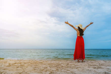 freedom woman in a red dress with arms raised on the sea beach