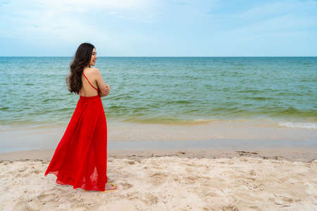 happy woman in red dress standing with arms crossed on the sea beach 免版税图像 - 155483414