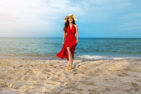 cheerful woman in red dress walking on the sea beach 免版税图像
