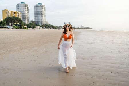 cheerful woman in bikini walking on the sea beach 免版税图像