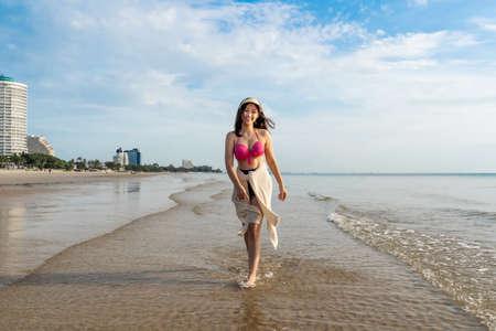cheerful woman in bikini walking on the sea beach 免版税图像 - 155483555