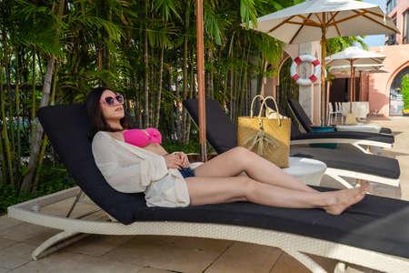 young woman in bikini lying on the deck chair near the pool
