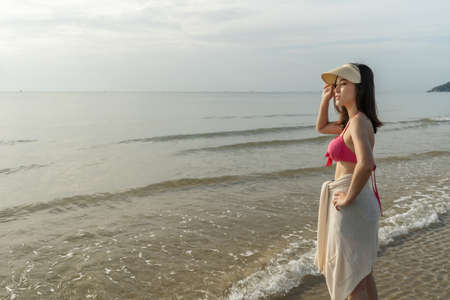 cheerful woman in bikini standing at the sea beach