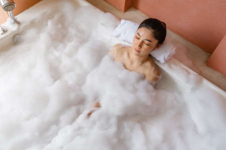 young woman relaxing in bathtub with eyes closed
