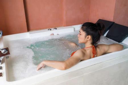woman in bikini relaxing inside a bathtub 免版税图像