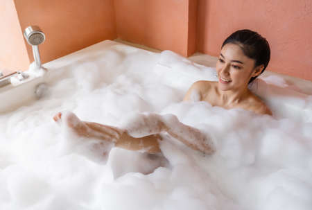 young woman relaxing and takes bubble bath in bathtub with foam 免版税图像 - 155483611
