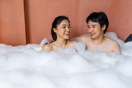 young couple relaxing and takes bubble bath in bathtub with foam 免版税图像 - 155483653