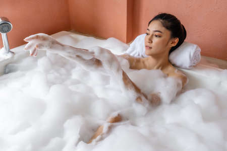young woman relaxing and takes bubble bath in bathtub with foam 免版税图像 - 155483666