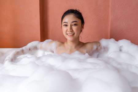 young woman relaxing and takes bubble bath in bathtub with foam 免版税图像 - 155483668