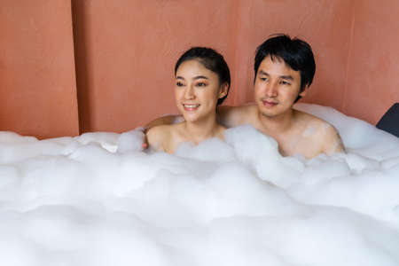 young couple relaxing and takes bubble bath in bathtub with foam