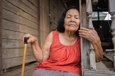 Thai elderly woman in round-necked sleeveless collar sitting lonely in old wooden home 免版税图像