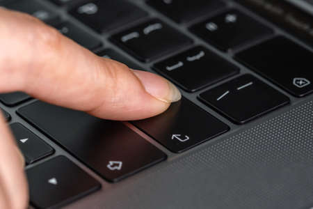close-up female hand pressing enter button on a laptop keyboard 免版税图像 - 155688945