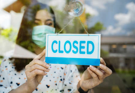 young woman owner with face mask closed store, effect of coronavirus (COVID-19) pandemic