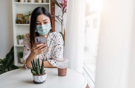 young woman wearing face mask for protection coronavirus (covid-19) and using smartphone in cafe 免版税图像 - 155850332