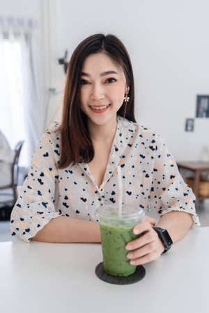 young woman drinking green tea latte in a cafe 免版税图像 - 155688609