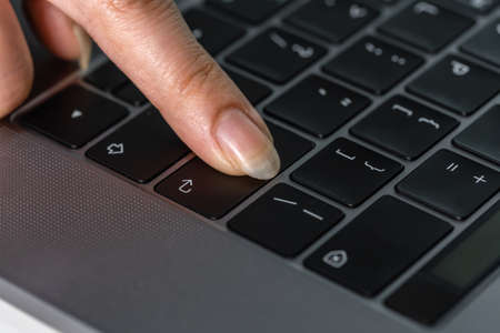 close-up female hand pressing enter button on a laptop keyboard 免版税图像 - 155688456
