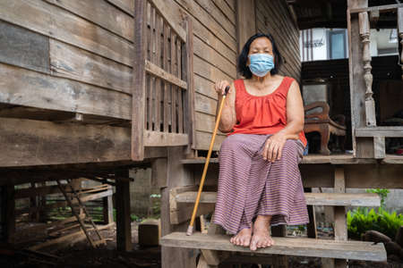 Thai elderly woman in round-necked sleeveless collar wearing medical mask for protect corona virus (covid-19) pandemic in old wooden home