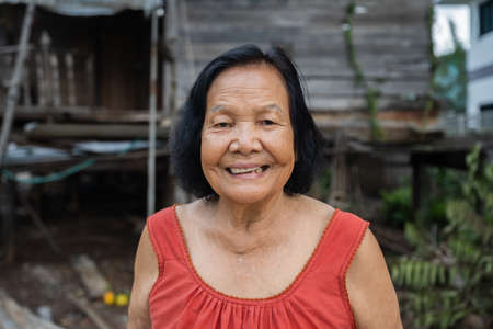 slow-motion of Thai elderly woman in round-necked sleeveless collar laughing in old wooden home 免版税图像