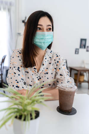 young woman wearing face mask for protection coronavirus (covid-19) and drinking chocolate milk in cafe 免版税图像 - 155850360