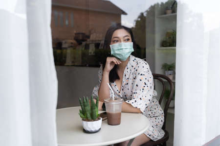 young woman wearing face mask for protection coronavirus (covid-19) and drinking chocolate milk in cafe 免版税图像 - 155850361