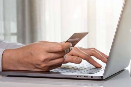 female hands holding a credit card to making online payment with laptop computer 免版税图像 - 155850362