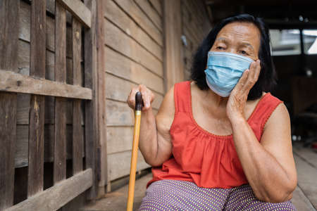 Thai elderly woman in round-necked sleeveless collar wearing medical mask for protect corona virus (covid-19) pandemic in old wooden home 免版税图像 - 155850364