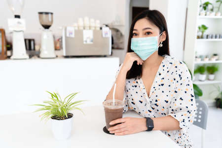 young woman wearing face mask for protection coronavirus (covid-19) and drinking chocolate milk in cafe 免版税图像 - 155850366