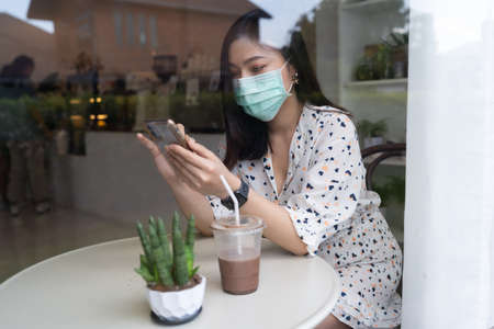 young woman wearing face mask for protection coronavirus (covid-19) and using smartphone in cafe 免版税图像