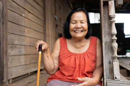 slow-motion of Thai elderly woman in round-necked sleeveless collar laughing in old wooden home 免版税图像 - 155850620