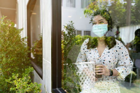 young woman wearing face mask for protection coronavirus (covid-19) and drinking chocolate milk in cafe 免版税图像 - 155850653