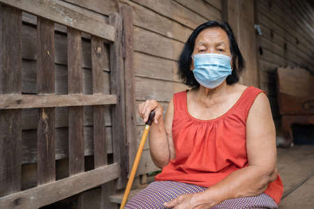 Thai elderly woman in round-necked sleeveless collar wearing medical mask for protect corona virus (covid-19) pandemic in old wooden home 免版税图像 - 155850677