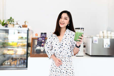 young woman drinking green tea latte in a cafe 免版税图像