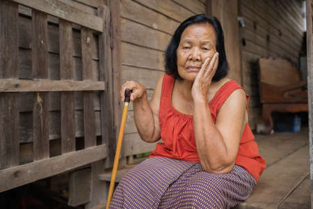 Thai elderly woman in round-necked sleeveless collar with headache and worried stressed face in old wooden home 免版税图像