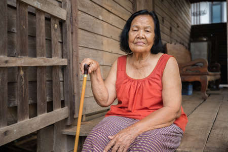 Thai elderly woman in round-necked sleeveless collar sitting lonely in old wooden home 免版税图像 - 155986429
