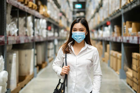 woman wearing medical mask in the warehouse store during coronavirus (covid-19) pandemic.