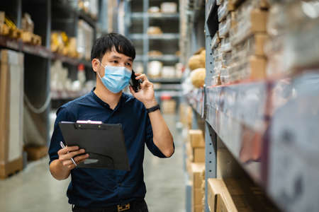 man worker with medical mask talking on a mobile phone and holding clipboard to checking inventory in the warehouse during coronavirus (covid-19) pandemic. Standard-Bild