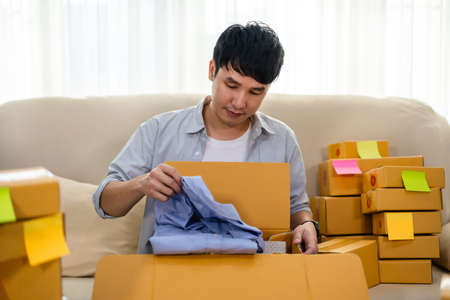 happy man open cardboard parcel box in the living room at home, purchase on online store