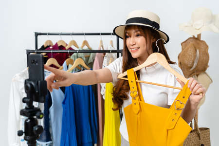 young woman selling clothes and hat online by smartphone live streaming, business online e-commerce at home
