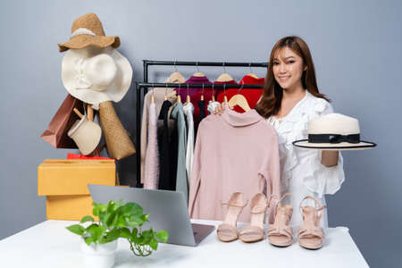 young woman selling clothes and accessories online live streaming, business online e-commerce at home