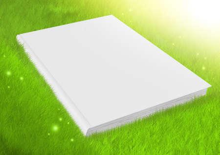White blank book in green fresh grass photo