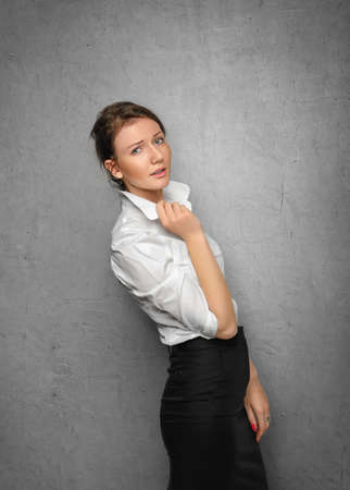 Pretty smiling young woman in office clothes on gray concrete wall. Business concept. photo