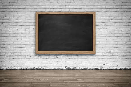 Blank black chalkboard in wooden frame on brick wall with wooden floor. Background and texture.