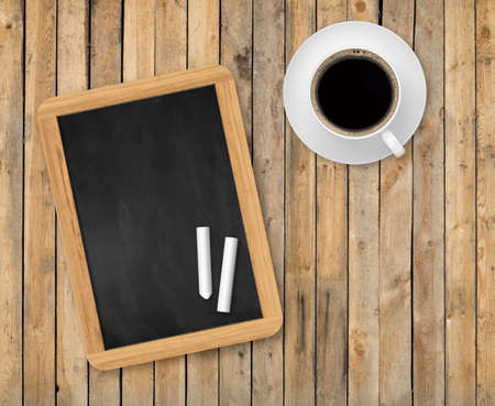Top view of wooden planks with blank black chalkboard, piece of chalk and cup of coffee Banco de Imagens