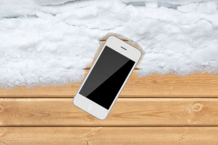 Top white wood office table with smartphone and snow photo