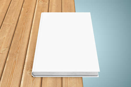 blanck: White textbook, situated on the edge of a wooden table